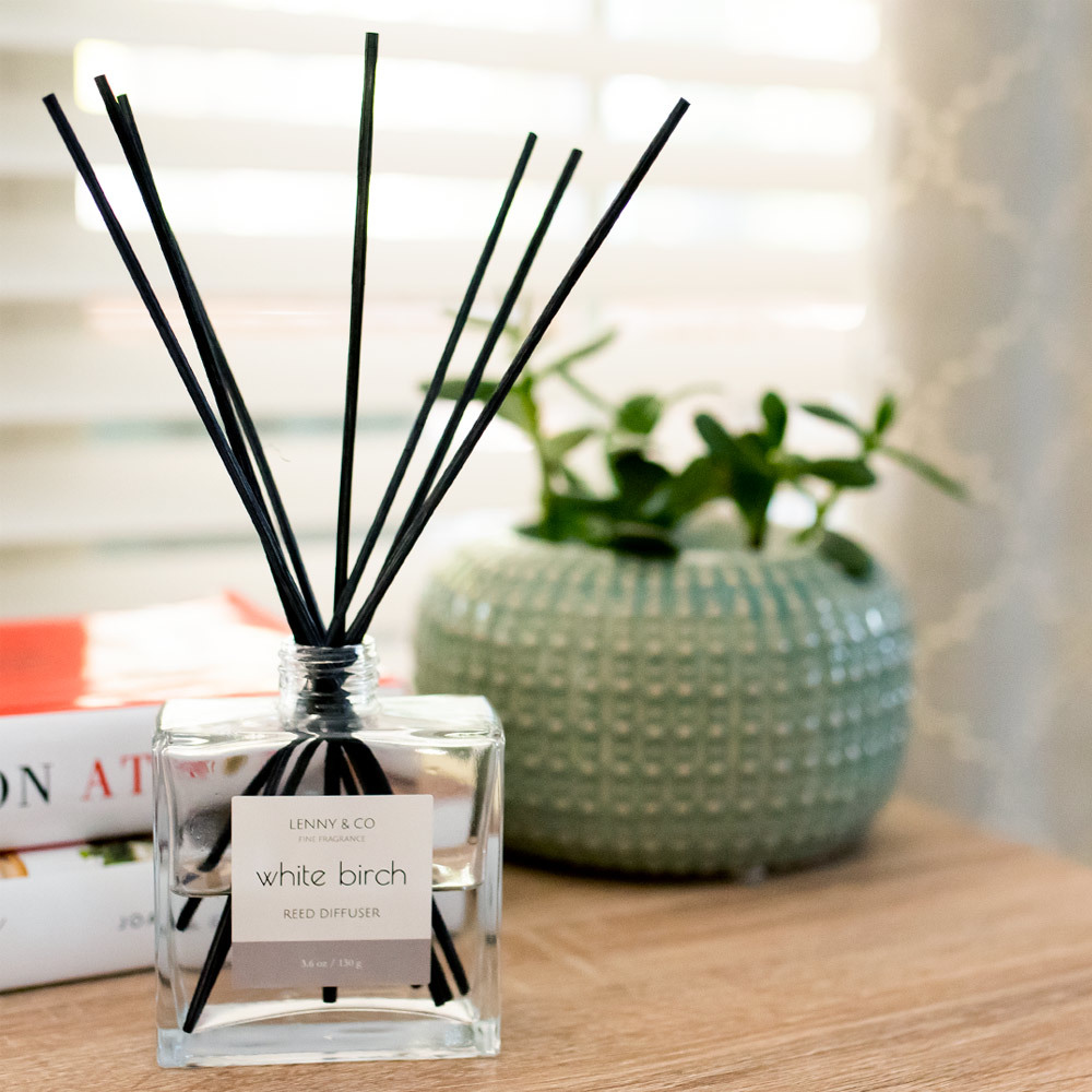 Black reeds in a glass diffuser bottle sitting on a counter