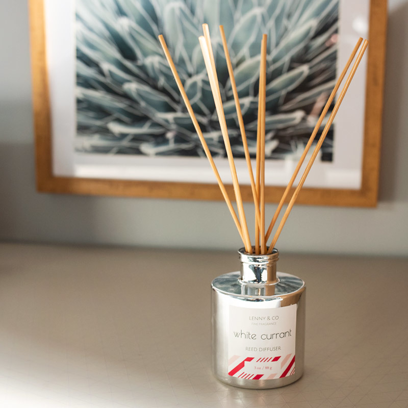 Silver Round Reed Diffuser Bottle with Natural Rattan Reeds sitting on a counter